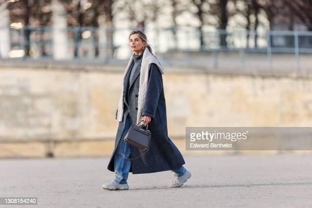Xenia Adonts wears golden earrings, a gray wool turtleneck pullover, a white knit wool oversized pullover, a gray long oversized wool coat, blue...