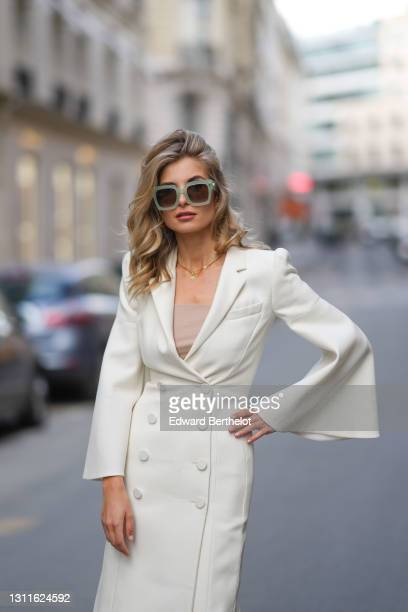 Xenia Adonts wears green Fendi sunglasses, a white long double breasted blazer jacket dress with flared sleeves, a golden bracelet, a golden...