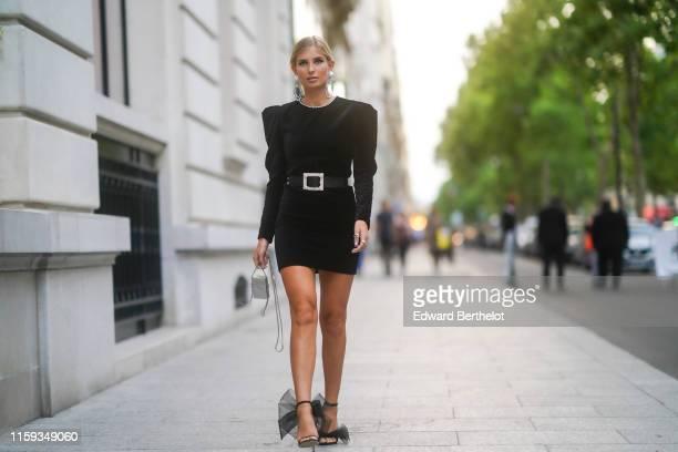 Xenia Adonts wears large earrings, rings, a rhinestone trimmed collar black mini dress, a black belt with a glittering rhinestone buckle, a grey...