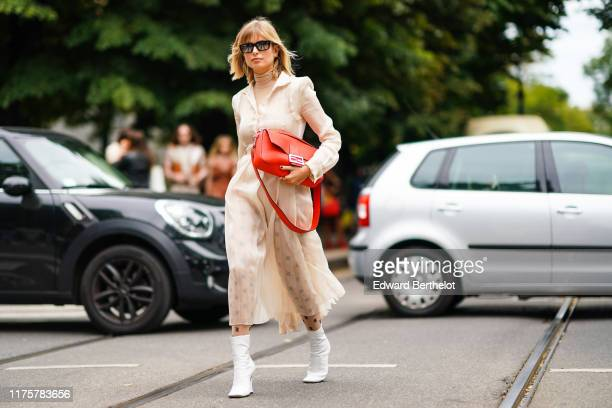 Xenia Adonts wears mirror sunglasses, a turtleneck top, a white lace mesh dress, Fendi tights with printed logos, white boots, an orange Fendi bag,...