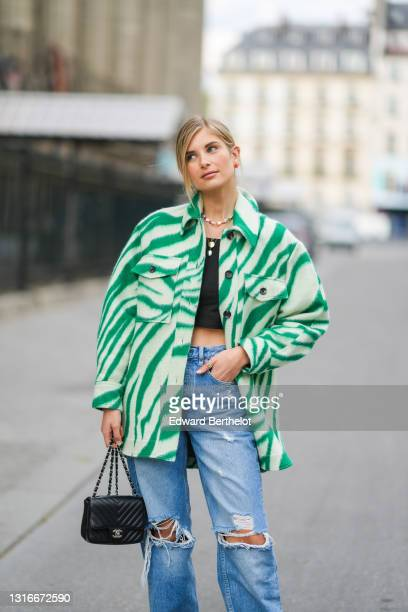Xenia Adonts wears red and gold earrings, a multicolors pearls necklace, silver and gold chain pendant necklaces, a black crop top, a green and pale...