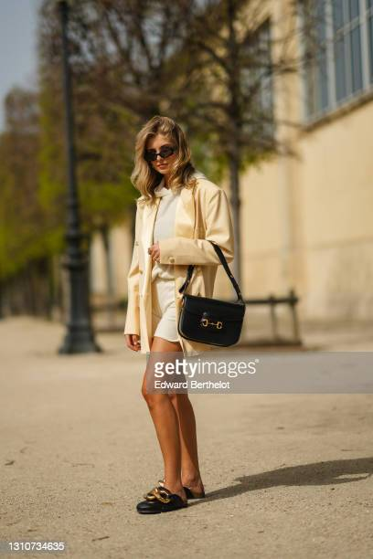 Xenia Adonts wears sunglasses, a beige oversized blazer jacket from Enveloppe, a white wool hoodie sweater and shorts from Uzwei, a black leather...