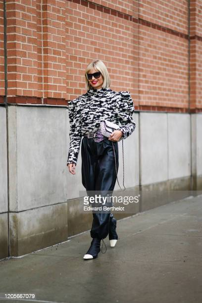 Xenia Adonts wears sunglasses, a black and white zebra print pullover with shoulder pads, a belt, large black leather pants, a white pearl beaded...