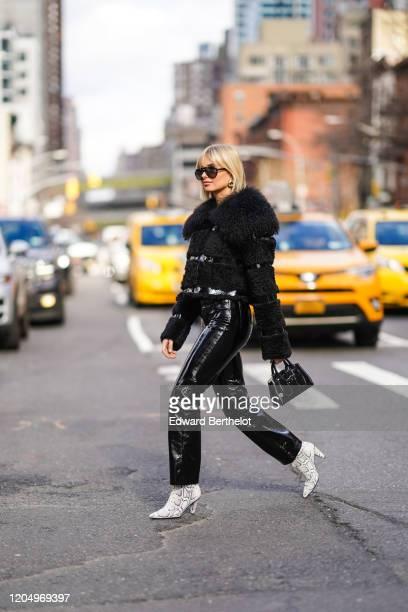Xenia Adonts wears sunglasses, a black fluffy coat, black shiny pvc pants, snake print boots, a black leather bag, outside Longchamp, during New York...