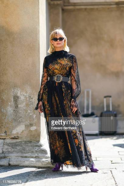 Xenia Adonts wears sunglasses, a black lace mesh dress with yellow floral print and embroidery, a black large leather belt outside the Etro show...