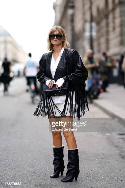 Xenia Adonts wears sunglasses, a black leather fringe jacket, a white shirt, a mini skirt, black boots, outside Giambattista Valli, during Paris...