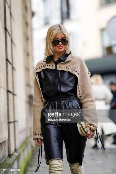 Xenia Adonts wears sunglasses, a black leather jumpsuit with a beige wool part and cropped leg parts, golden bracelets, outside Altuzarra, during...