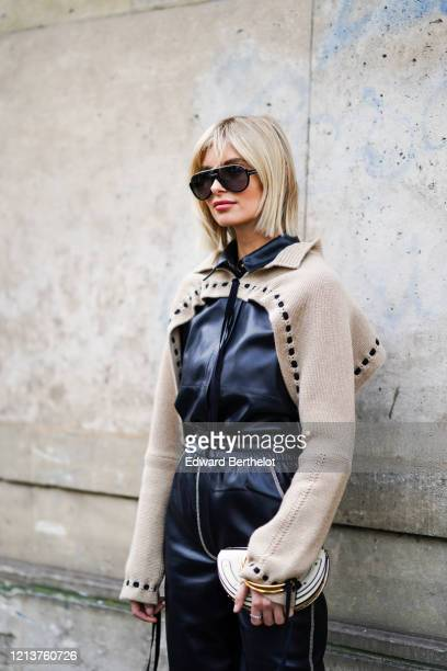 Xenia Adonts wears sunglasses, a black leather jumpsuit with a beige wool part and cropped leg parts, a Chloe bag, golden bracelets, outside...
