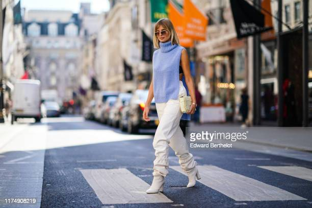 Xenia Adonts wears sunglasses, a blue wool sleeveless turtleneck pullover, white pants, a bag featuring several attached squares, white boots, during...