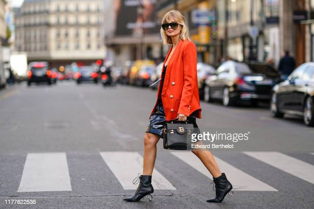 Xenia Adonts wears sunglasses a red oversized blazer jacket a Balmain logo bag a black dress black leather boots with metallic heels outside Balmain...