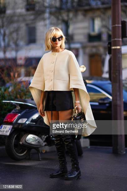 Xenia Adonts wears sunglasses, a white cape/poncho, a black short skirt, black leather thigh high boots, a crocodile pattern leather bag, outside...