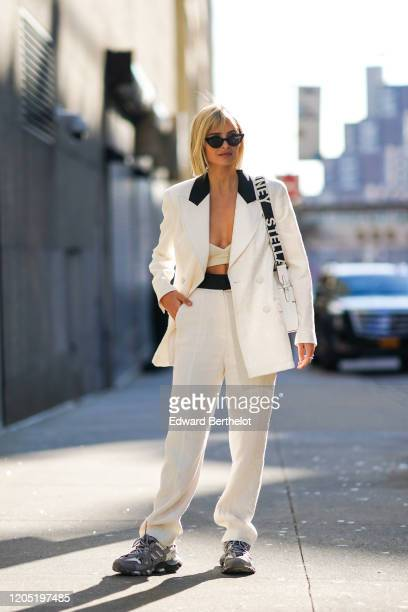 Xenia Adonts wears sunglasses, a white oversized jacket with black collar, white pants, sneakers, a bag, outside Tory Burch, during New York Fashion...
