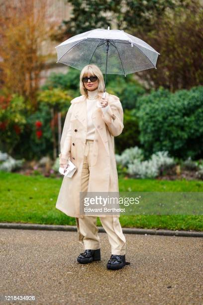 Xenia Adonts wears sunglasses, a white turtleneck pullover, a golden chain necklace, a beige clear long coat, beige pants, black shoes outside Maison...