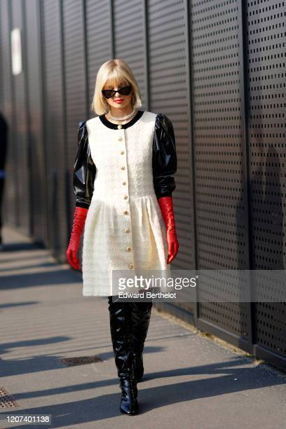 Xenia Adonts wears sunglasses, a white tweed dress with black shiny puff sleeves, a necklace, black shiny pvc thigh high boots, red gloves, outside...