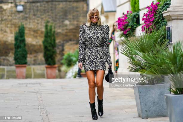 Xenia Adonts wears sunglasses a zebra print pattern dress with padded shoulders a black bag black leather boots during London Fashion Week September...