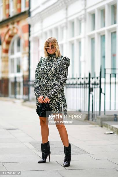 Xenia Adonts wears sunglasses, a zebra print pattern dress with padded shoulders, a black bag, black leather boots, during London Fashion Week...