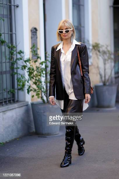 Xenia Adonts wears white sunglasses, a black leather jacket, a white shirt, leather shorts, black shiny long pointy boots, outside Tod's, during...