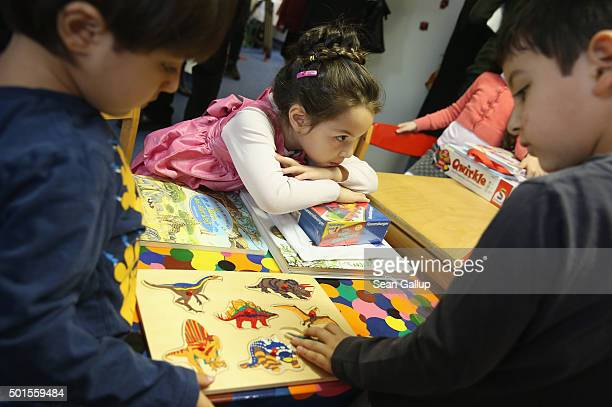 Xenia from Moldova and two young brothers from Syria look at games and books during the presentation of a new initiative to help children of refugees...