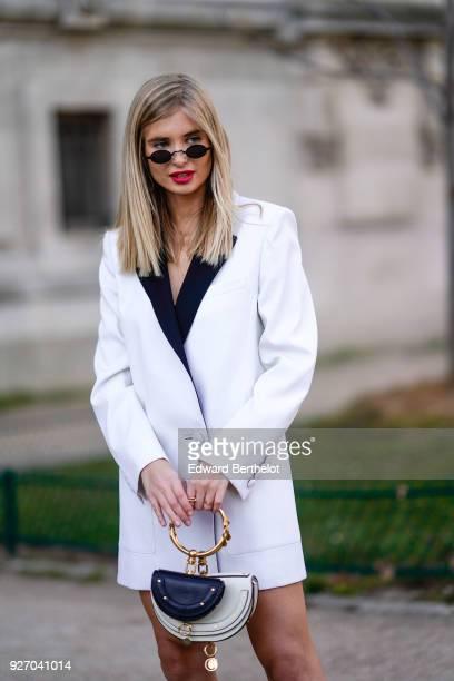 Xenia Van Der Woodsen 'Overdose' wears a white oversized blazer jacket dress sunglasses a double black and white Chloe bag black boots during Paris...