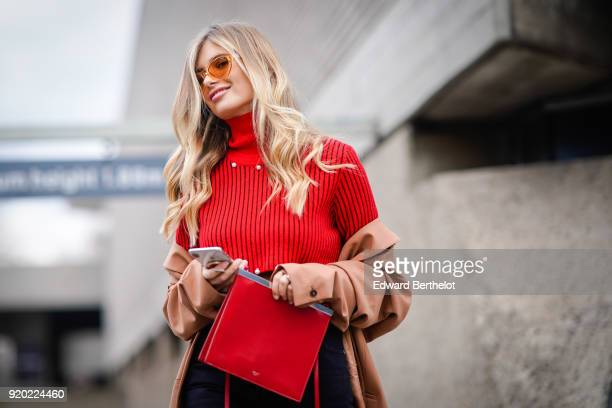 Xenia Van Der Woodsen Overdose wears sunglasses a red turtleneck bare belly pullover jeans white boots a brown coat during London Fashion Week...