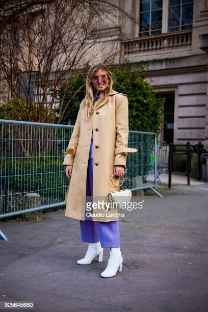 Xenia Van Der Woodsen, wearing a beige trench and white heels boots, is seen in the streets of Paris before the Rochas show during Paris Fashion Week...