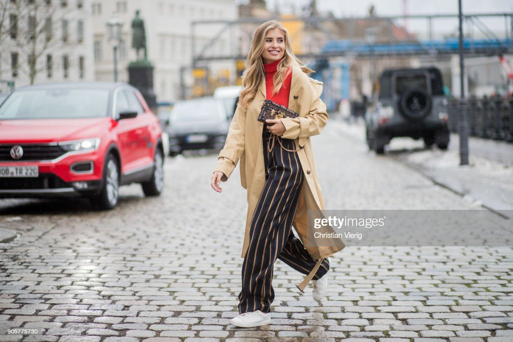 Xenia van der Woodsen wearing Louis Vuitton shoes, striped By Malene Birger pants, trench coat Topshop, Marc Cain top, Celine earrings, Louis Vuitton clutch is seen during the Berlin Fashion Week January 2018 at Bauakademie on January 16, 2018 in Berlin, Germany.