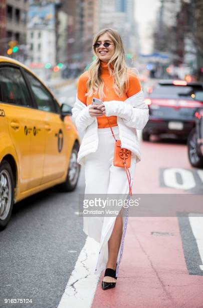 Xenia van der Woodsen wearing orange turtleneck white pants seen outside Tory Burch on February 9 2018 in New York City