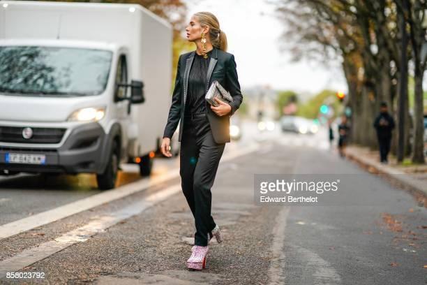 Xenia Van der Woodsen wears a black blazer jacket a black top black pants a silver bag pink glitter shoes outside John Galliano during Paris Fashion...