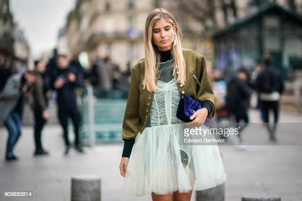 Xenia Van Der Woodsen wears a green bomber jacket a mesh lace dress black boots a turtleneck top a black clutch outside Viktor Rolf during Paris...