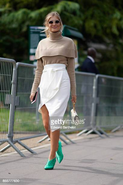 Xenia Van Der Woodsen 'Xenia Overdose' wears sunglasses a camel ruffle top sunglasses a white skirt green shoes outside Issey Miyake during Paris...