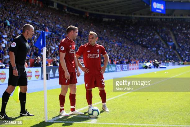 Xherdan Shaqiri and James Milner of Liverpool in discussion over a corner as the linesman looks on during the Premier League match between Leicester...
