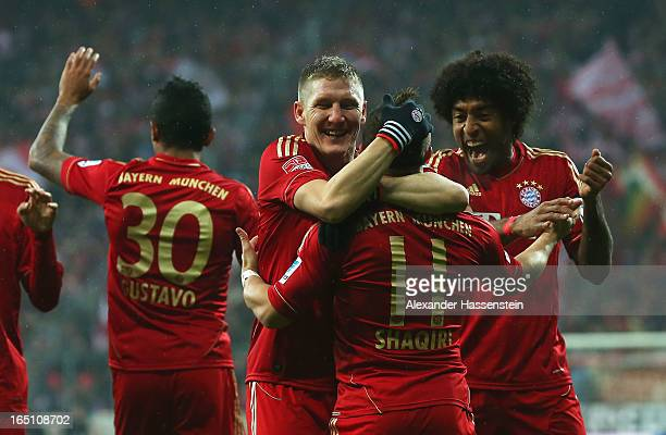 Xherdan Shaqiri of Bayern Muenchen is congratulated by Bastian Schweinsteiger and Dante after scoring the opening goal during the Bundesliga match...