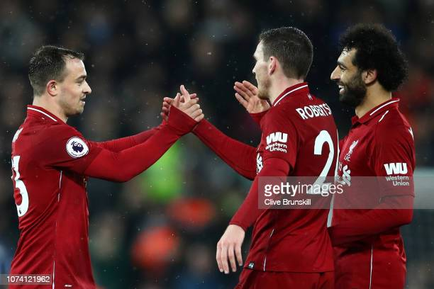 Xherdan Shaqiri of Liverpool celebrates with team mates Andy Robertson and Mohamed Salah of Liverpool following their side's victory in the Premier...