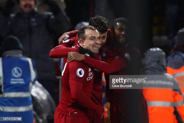 Xherdan Shaqiri of Liverpool celebrates with teammates Roberto Firmino and Georginio Wijnaldum after scoring his team's third goal during the Premier...