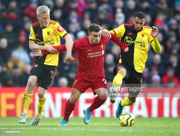 Xherdan Shaqiri of Liverpool is tackled by Will Hughes and Etienne Capoue of Watford during the Premier League match between Liverpool FC and Watford...