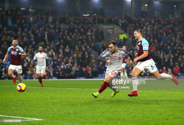 Xherdan Shaqiri of Liverpool scores his team's third goal under pressure from James Tarkowski of Burnley during the Premier League match between...