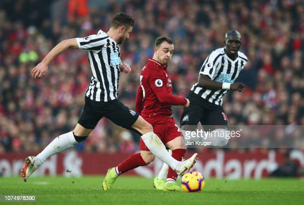 Xherdan Shaqiri of Liverpool takes on Paul Dummett and Mohamed Diame of Newcastle United during the Premier League match between Liverpool FC and...