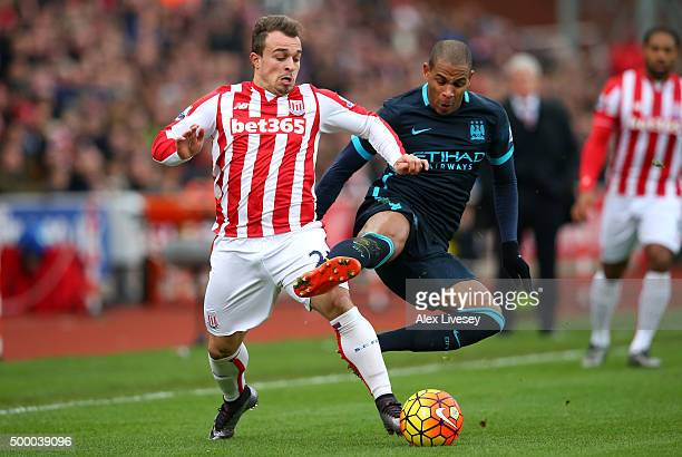 Xherdan Shaqiri of Stoke City and Fernando of Manchester City compete for the ball during the Barclays Premier League match between Stoke City and...