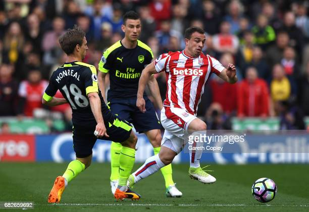 Xherdan Shaqiri of Stoke City attempts to escape a challenge from Nacho Monreal of Arsenal during the Premier League match between Stoke City and...