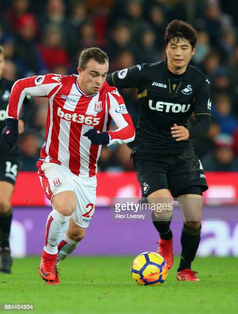 Xherdan Shaqiri of Stoke City attempts to get away from Ki SungYueng of Swansea City during the Premier League match between Stoke City and Swansea...