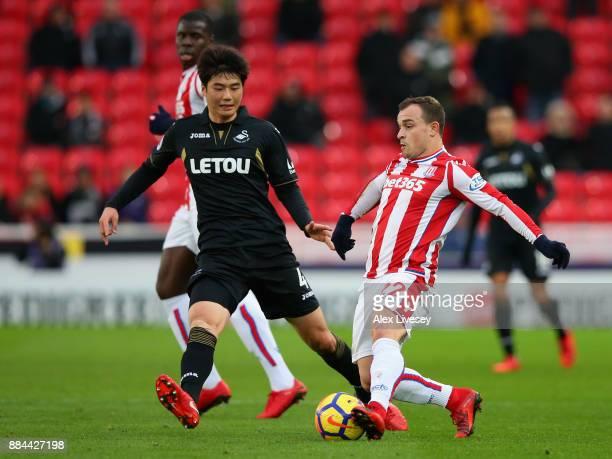Xherdan Shaqiri of Stoke City is challenged by Ki SungYueng of Swansea City during the Premier League match between Stoke City and Swansea City at...
