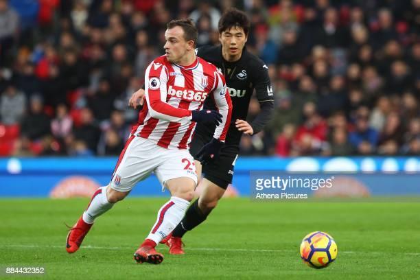 Xherdan Shaqiri of Stoke City is marked by Ki Sungyueng of Swansea City during the Premier League match between Stoke City and Swansea City at the...