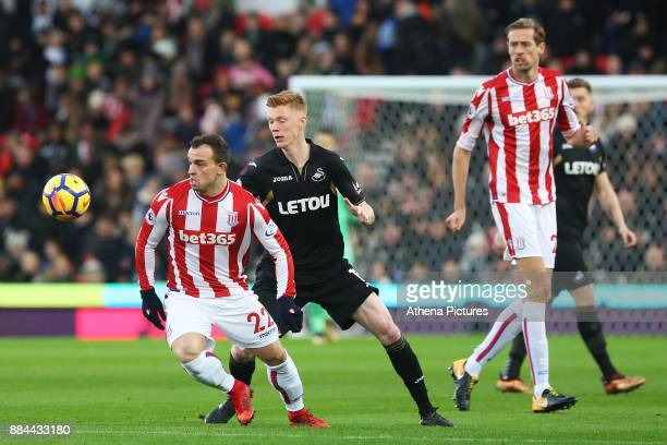 Xherdan Shaqiri of Stoke City is marked by Sam Clucas of Swansea City during the Premier League match between Stoke City and Swansea City at the...