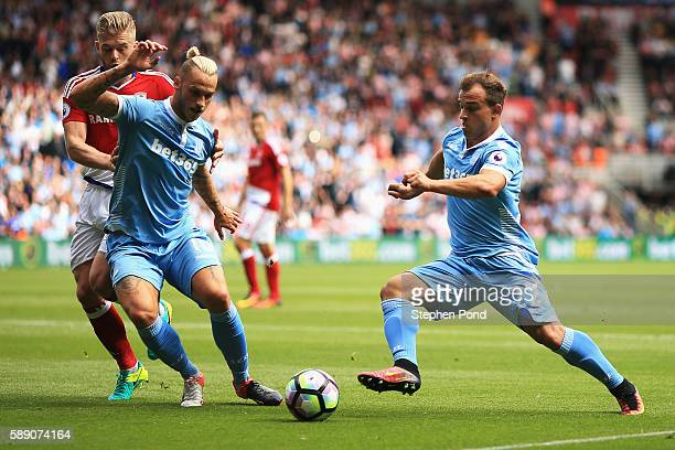 Xherdan Shaqiri of Stoke City takes the ball past Adam Clayton of Middlesbrough with help from his team mate Marko Arnautovic of Stoke City during...