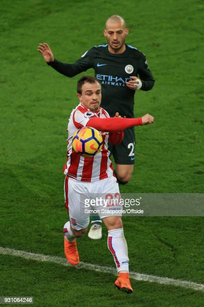 Xherdan Shaqiri of Stoke punches the ball in frustration as David Silva of Man City looks on during the Premier League match between Stoke City and...
