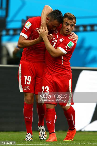 Xherdan Shaqiri of Switzerland celebrates scoring his team's second goal with his teammate Josip Drmic during the 2014 FIFA World Cup Brazil Group E...