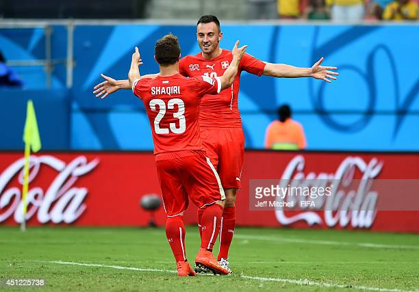 Xherdan Shaqiri of Switzerland celebrates scoring his team's third goal with his teammate Josip Drmic of Switzerland to complete his hat trick during...