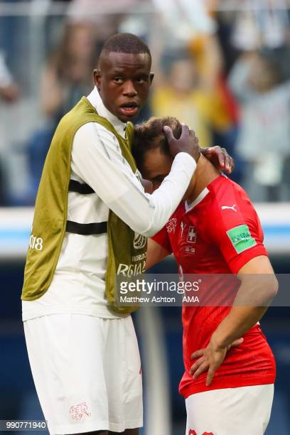 Xherdan Shaqiri of Switzerland is consoled by Deni Zakaria of Switzerland at the end of the 2018 FIFA World Cup Russia Round of 16 match between...