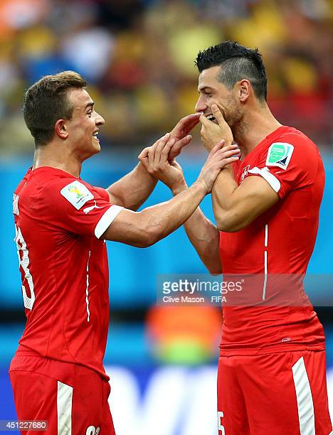 Xherdan Shaqiri of Switzerland speaks to Blerim Dzemaili as he is replaced during the 2014 FIFA World Cup Brazil Group E match between Honduras and...