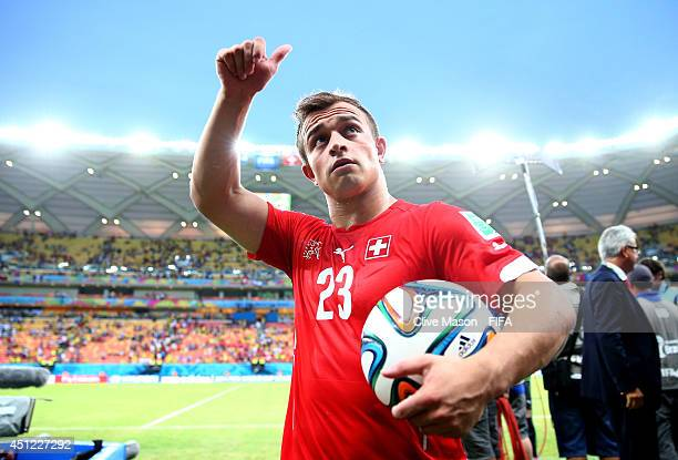 Xherdan Shaqiri of Switzerland walks off the pitch with the match ball as he completed a hat trick after the 3-0 win in the 2014 FIFA World Cup...